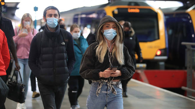 Commuters in masks arriving at Leeds railway station today