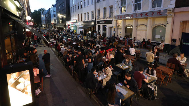 People eating on restaurant tables placed outside on Frith St in Soho, London
