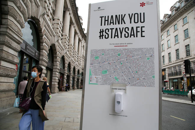 File photo: A woman wearing a face mask walks past a hand sanitizer station on Regents Street