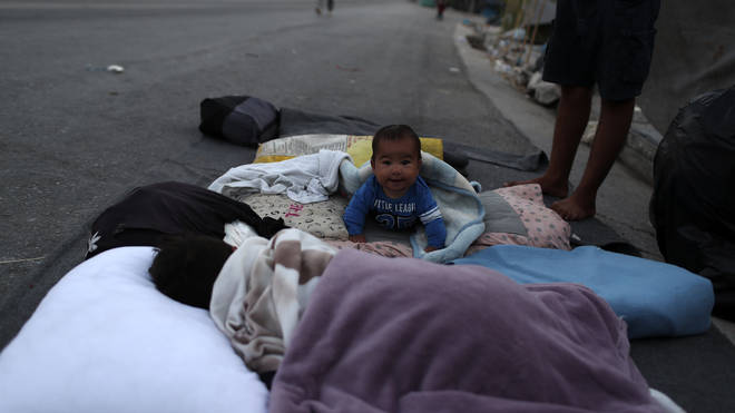 A baby crawls as migrants remain camped out on a roa