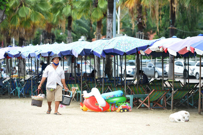 A vender carries food for sale at Pattaya beach in Chonburi province, Thailand