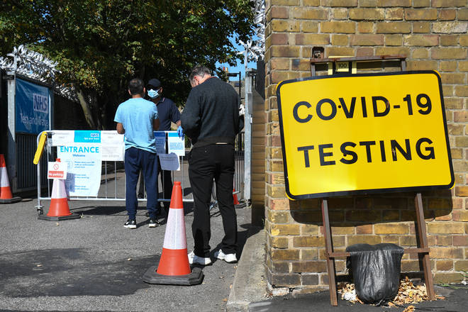 People queue up outside a coronavirus testing centre offering walk-in appointments in east London