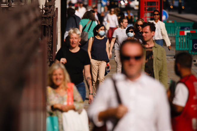 People, some wearing face masks, walk along Piccadilly in London