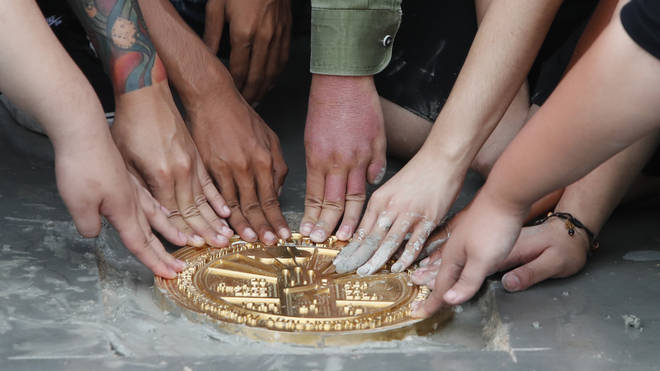 Pro-democracy student leaders install a plaque declaring 'This country belongs to the people' at the Sanam Luang field in Bangkok