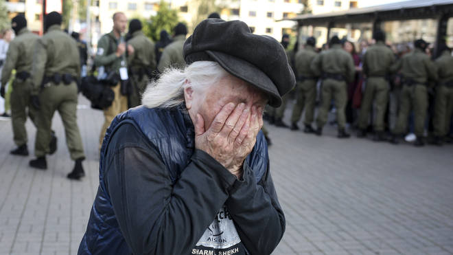 An elderly woman reacts as police officers detain women during an opposition rally in Minsk, Belarus