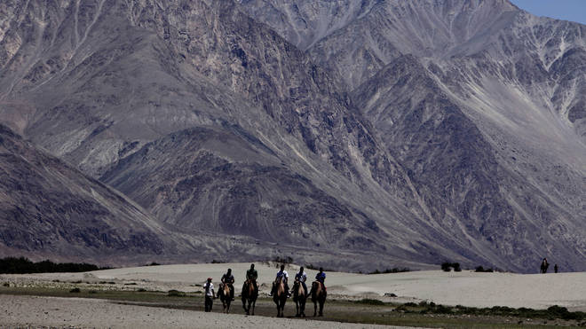 Tourists ride camels at Nubra valley, in the disputed region of Ladakh, India (Channi Anand/AP)