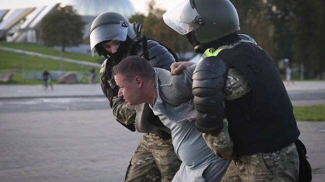 Riot police detain a protester