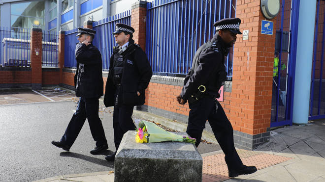 Police walk past flowers left in tribute to the fallen officer