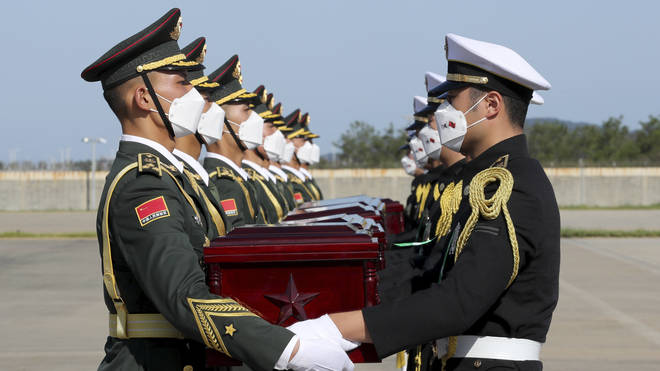 Chinese honour guard members, left, receive caskets containing the remains of Chinese soldiers from South Korean honour guards during the handing over ceremony at the Incheon International Airport in Incheon, South Korea
