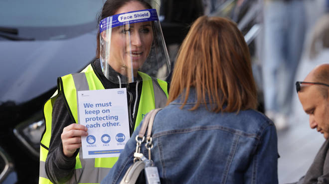 A woman handing out leaflets promoting the new NHS Covid-19 app in Liverpool