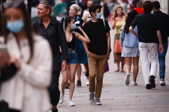 Shoppers, some wearing face masks, walk along Regent Street in London