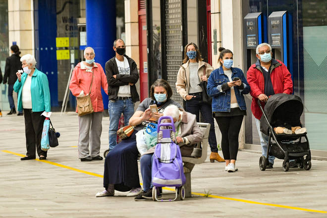 File photo: People wear face coverings as they queue for shops and businesses in Cardiff