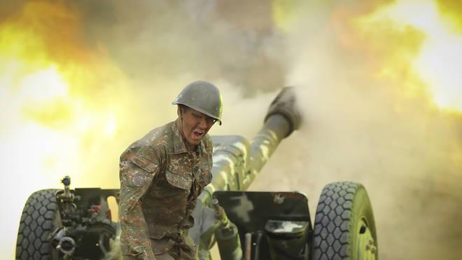 An Armenian serviceman fires a cannon towards Azerbaijan positions in the self-proclaimed Republic of Nagorno-Karabakh