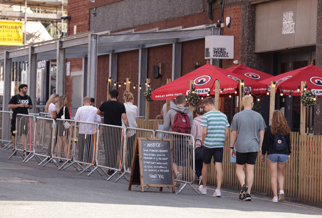 People socially distancing queueing to enter Baltic Market in Liverpool