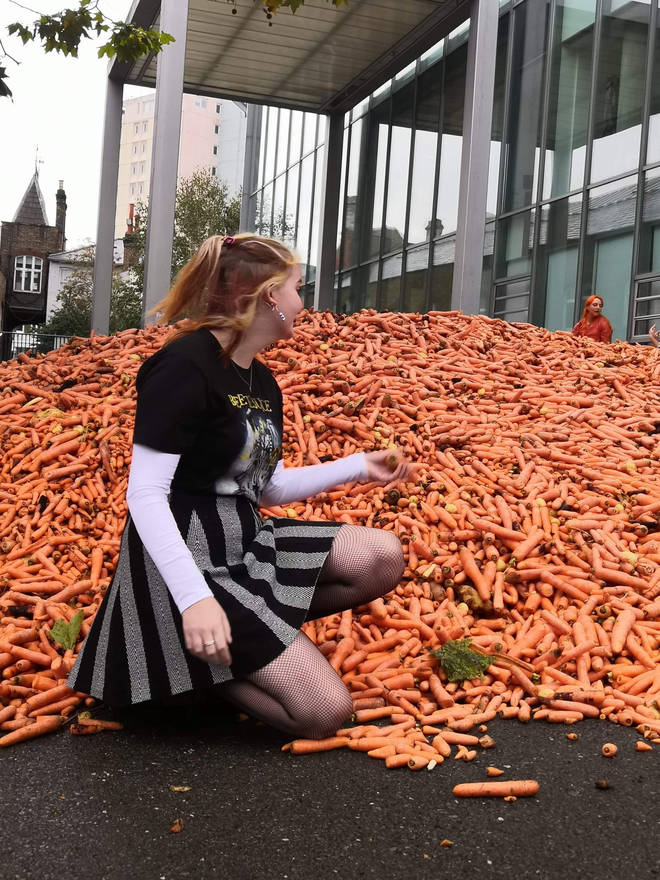 Some people took photos on top of or in front of the pile of carrots