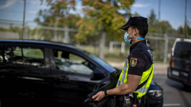 A police officer stands guard at a checkpoint in the Orcasitas neighbourhood in Madrid
