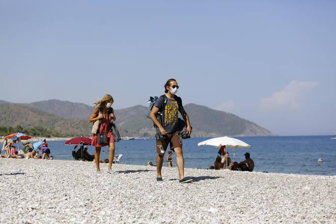 People wearing face masks walk on a beach in Antalya, Turkey