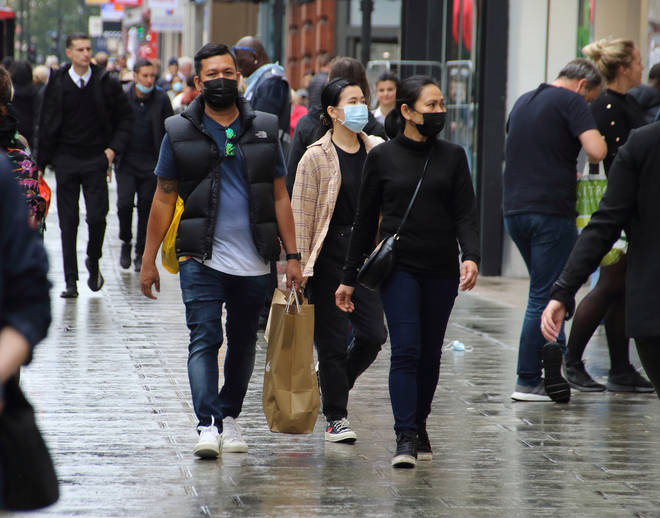 People walk along Oxford Street while while wearing face masks