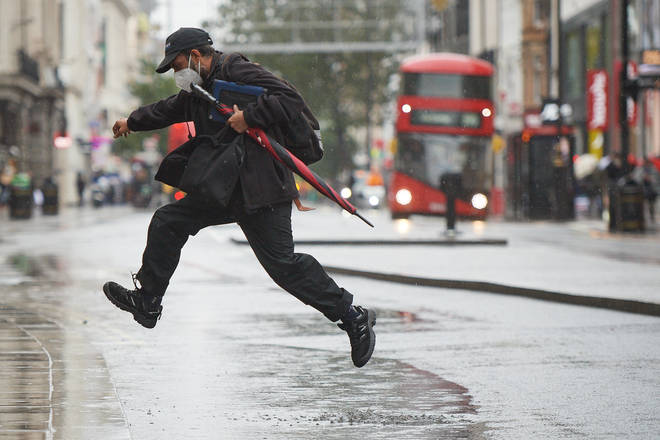 A man jumps over a puddle in London as Storm Alex brings heavy rain to the UK