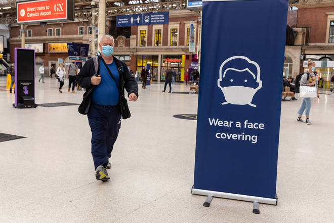 File photo: Passengers in protective face masks are seen walking on a sideway at Victoria Station