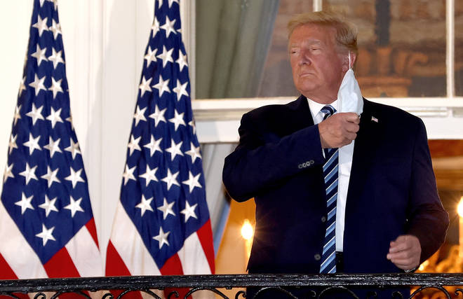 President Donald Trump removes his mask upon return to the White House