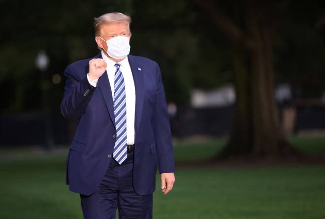 President Donald Trump gestures upon return to the White House from Walter Reed National Military Medical Center