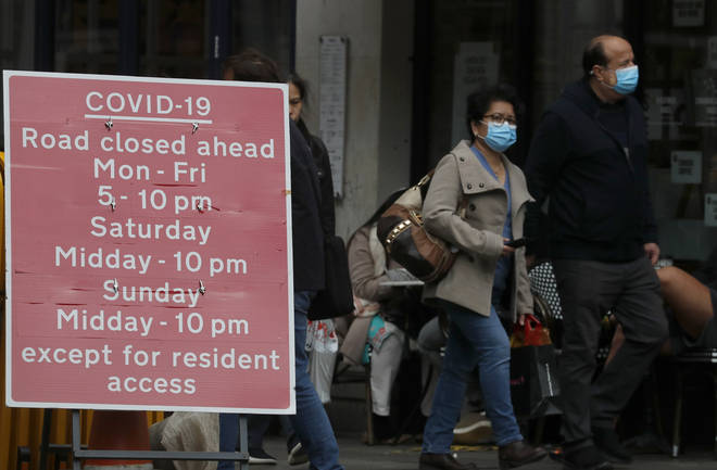 People walk past a sign that refers to COVID-19 closures in London