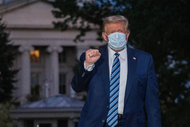 President Donald Trump poses for the cameras as he returns to the White House in a mask after his stay in hospital for coronavirus