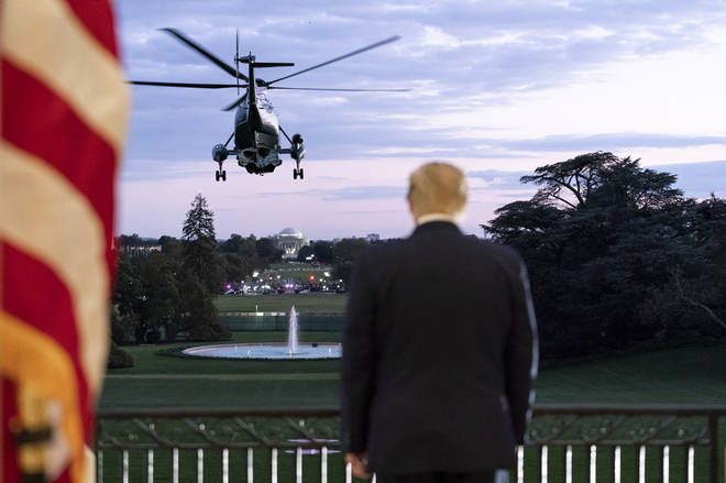 President Trump salutes Marine One from the Blue Room Balcony of the White House after returning from Walter Reed National Military Medical Center