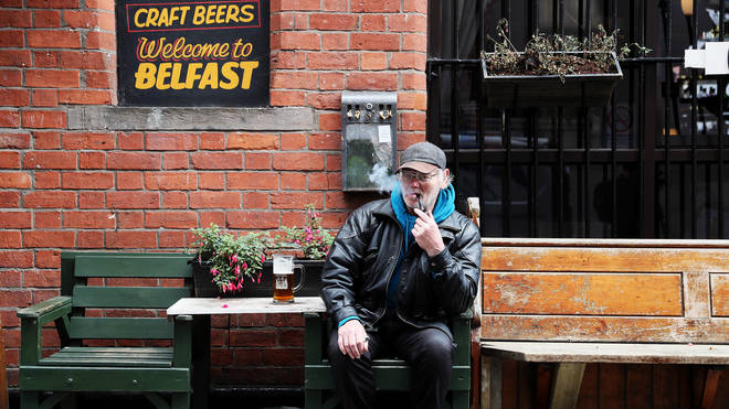 David Legge, from Belfast, enjoys a pint and a pipe outside Bittles Bar in Belfast
