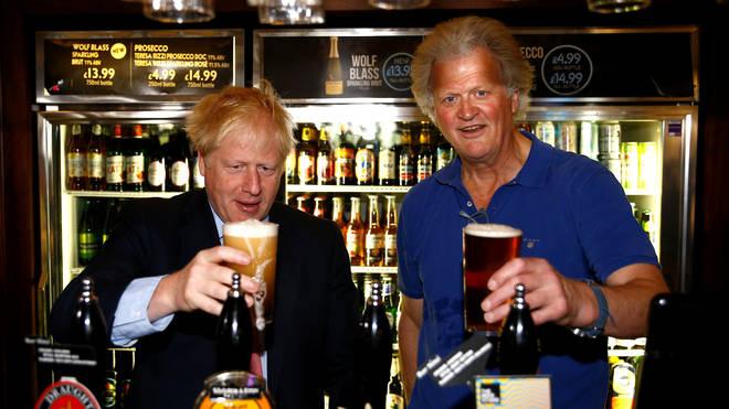 Boris Johnson and Tim Martin behind the bar at a Wetherspoon pub