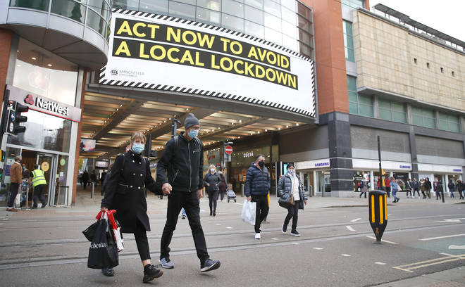 File photo: People wearing face masks walk past a advertisement on Market Street in Manchester