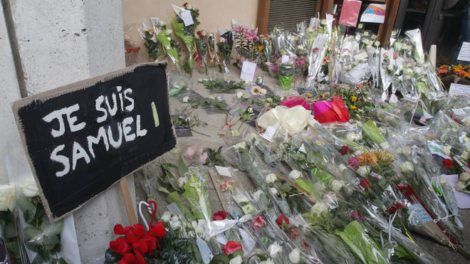 A poster reading I am Samuel and flowers lay outside the school where history teacher Samuel Paty was working in Conflans-Sainte-Honorine, northwest of Paris