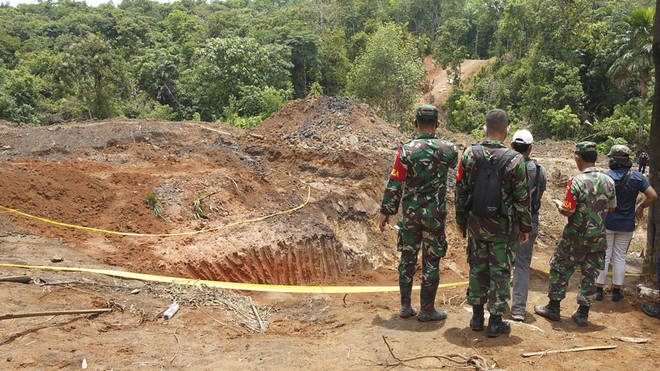 Military personnel inspect the site of a landslide at a coal mine in Muara Enim, South Sumatra