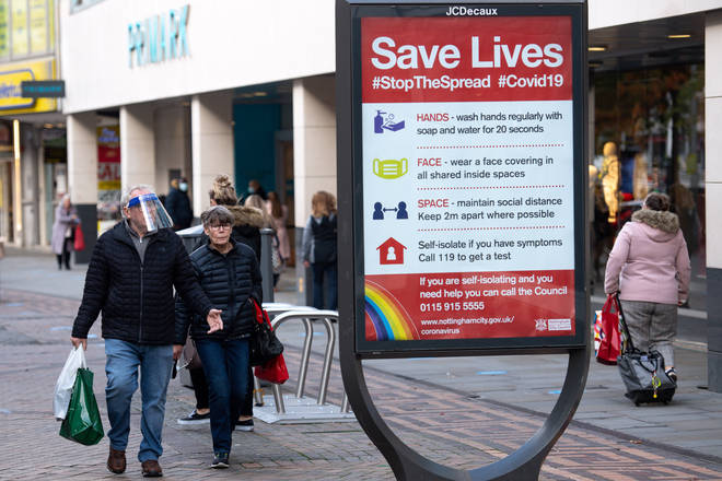 A man wearing a face shield walks past a coronavirus advice sign in Nottingham city centre