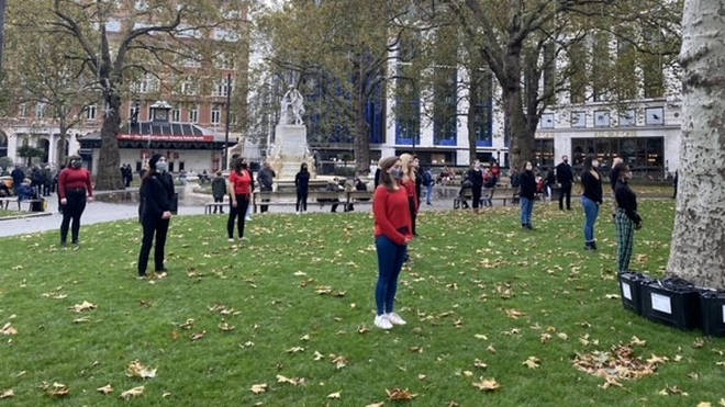 The protesters were seen standing socially-distanced with face masks on in Leicester Square