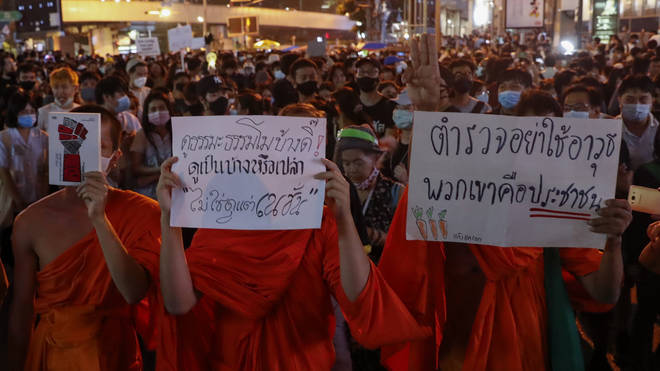 Buddhist monks supporters of pro-democracy protesters display placards as they march to the German Embassy in central Bangkok, Thailand (Gemunu Amarasinghe/AP)