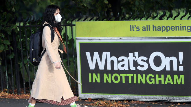 A woman in a mask walks past a sign reading: 'What's On! In Nottingham'