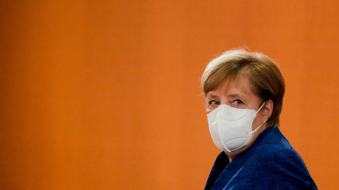 German Chancellor Angela Merkel looks sideways wearing a face mask