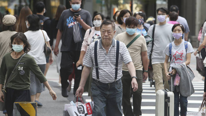People wear face masks to protect against the spread of coronavirus as they walk through a shopping district in Taipei, Taiwan (Chiang Ying-ying/AP)