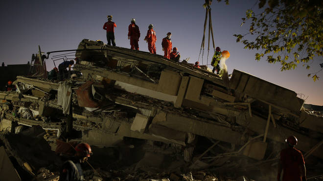 Members of rescue services search for survivors in the debris of a collapsed building in Izmir, Turkey