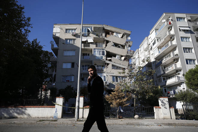 A local resident walks past destroyed buildings in Izmir, Turkey