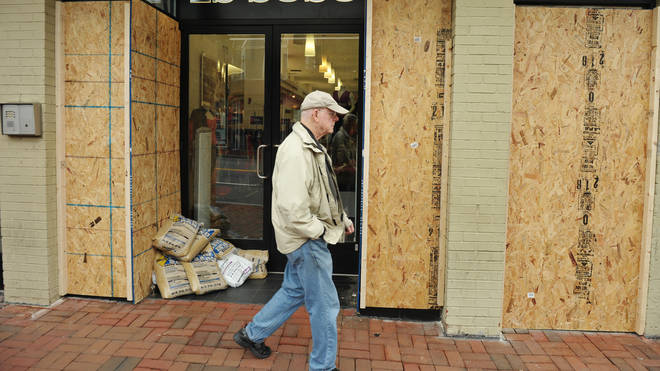 A pedestrian walks past a boarded up shop in Washington DC