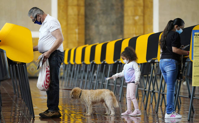 As Thomas Frieburger, left, and Lourdes Santos, right, vote on Election Day, Santos' daughter Sofia, 4, tries to get the attention of Frieburger's dog Lucky at a polling place at Union Station,