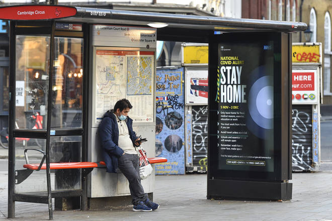 A man using his phone at a bus stop in Cambridge Circus, London