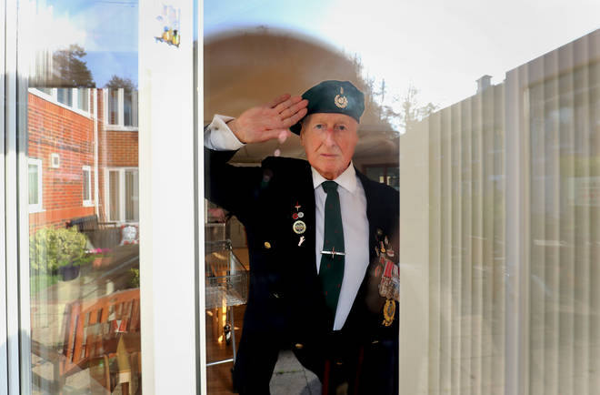 George Bradford, 90, a former Royal Marine stands behind a window at the RBLI home in Aylesford, Kent, during the two minutes silence to pay his respects on Remembrance Sunday.
