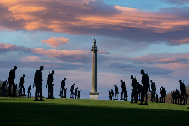 Silhouetted soliders at sunrise with Blenheim Palace's Column of Victory in the background