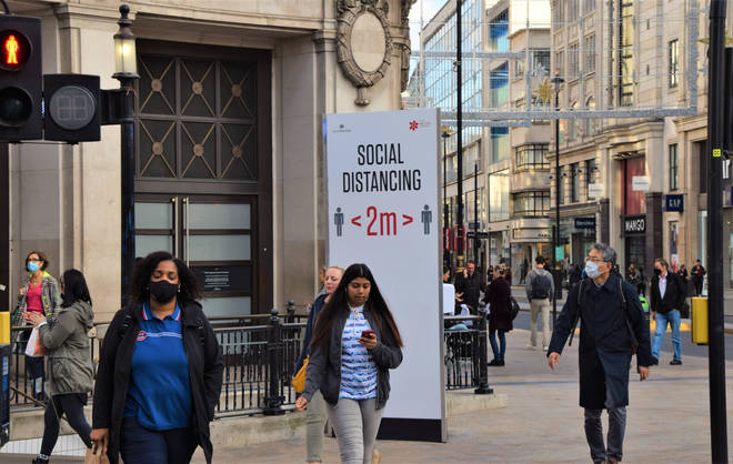 File photo: People wearing face masks as a precaution walking past a social distancing sign on Oxford Street