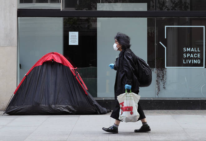 File photo: A woman walking past a homeless person's tent erected outside a furniture store in Tottenham Court Road, London