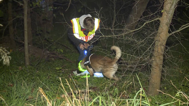 A policeman with a tracker dog searching for a missing man in Berlin